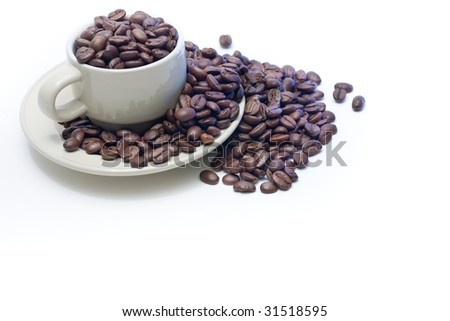 Coffee cup filled with coffee beans, which have spilled over onto the saucer and beyond, isolated on white.