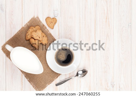Coffee cup, heart shaped gingerbread cookies and milk pitcher. On white wooden table with copy space - stock photo