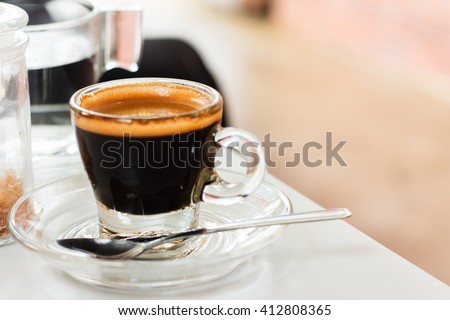 Coffee cup. Hot espresso with golden crema on white table in cafe. - stock photo