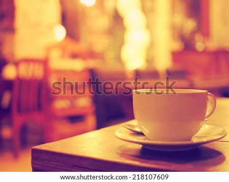 coffee cup in coffee shop vintage warm color tone - stock photo
