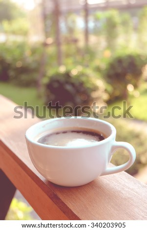 Coffee cup in the garden with vintage color style - stock photo