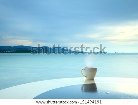 Coffee cup in the morning on  terrace facing seascape  - stock photo