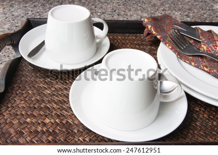 Coffee cup, knife, fork, plate on wooden tray  - stock photo