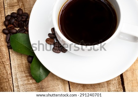 Coffee cup, leaves and beans on wood background. Coffee background.