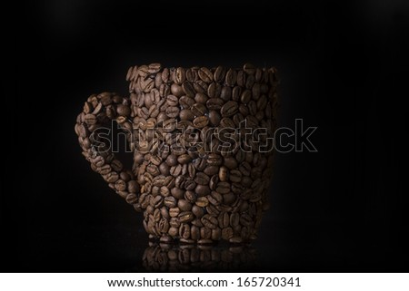 Coffee cup made of coffee beans on black background - stock photo