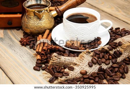 coffee cup,  metal turk and coffee beans on a wooden background - stock photo