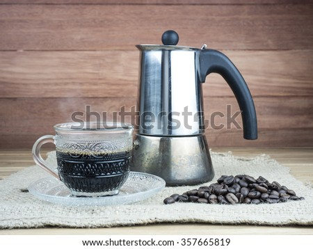 Coffee cup, moka pot and coffee beans on sack, wooden background.