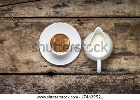 Coffee. Cup of Coffee with Milk Jug on Wood Background.  Top View - stock photo