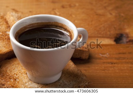 Coffee cup of  espresso with toast on wooden table