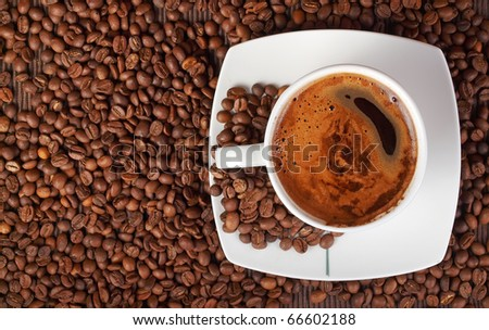 Coffee cup on a lot of coffee beans - stock photo