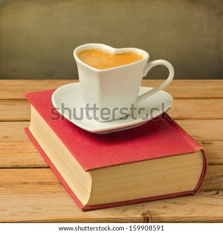 Coffee cup on book. Heart shape cup symbol of love - stock photo
