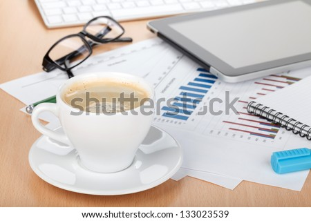 Coffee cup on contemporary workplace with financial papers, computer and office supplies - stock photo