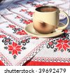 Coffee cup on embroidery tablecloth - stock photo