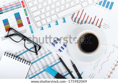 Coffee cup on financial papers, computer and office supplies - stock photo