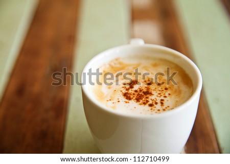 Coffee cup on grunge wood floor - stock photo