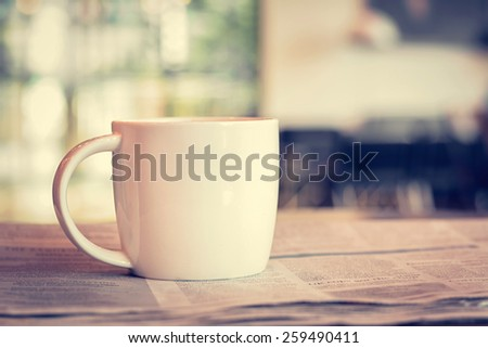 Coffee cup on newspaper in coffee shop - vintage (retro) style color effect - stock photo