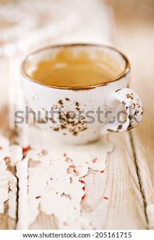 Coffee cup on old wooden table, shallow dof - stock photo
