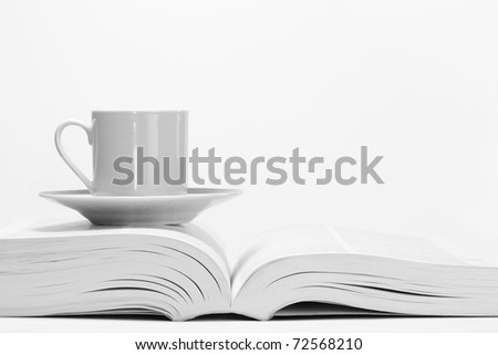 Coffee cup on open book. - stock photo
