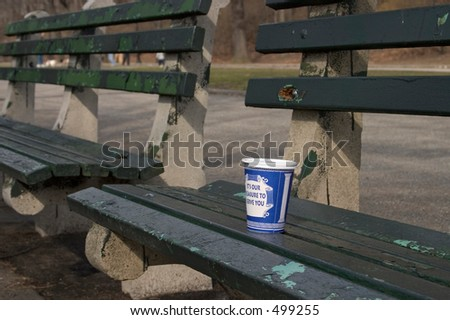 coffee cup on park bench - stock photo