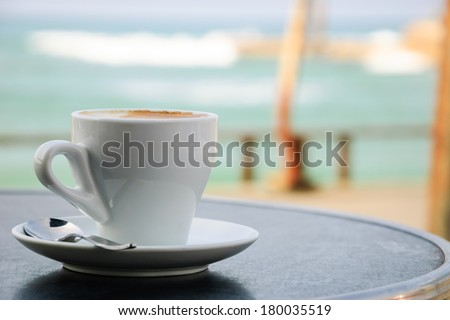 Coffee cup on round table in cafe terrace on the old pier with rusty railing and the view on the sea with waves in sunny day. - stock photo