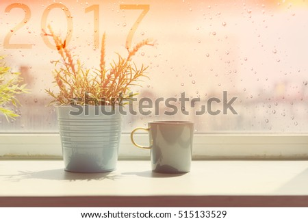 Coffee cup on table with rain drop and 2017 text on window background