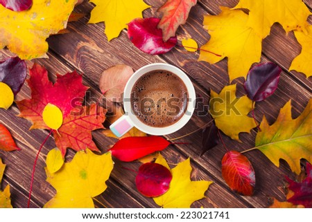 coffee cup on the autumn fall leaves on wooden background  - stock photo