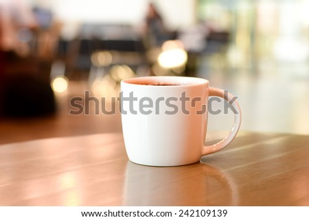Coffee cup on the table in coffee shop blur background - stock photo