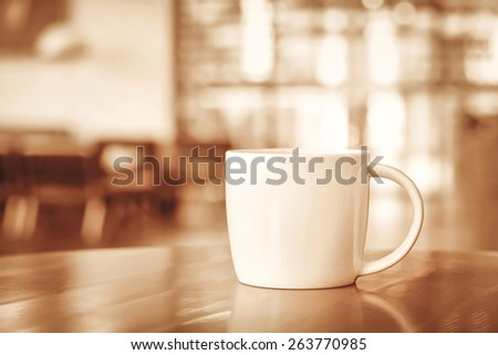 Coffee cup on the table in coffee shop - sepia tone, soft focus - stock photo