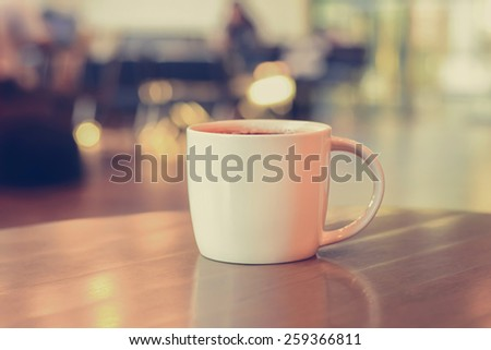 Coffee cup on the table in coffee shop - vintage style color, soft focus - stock photo