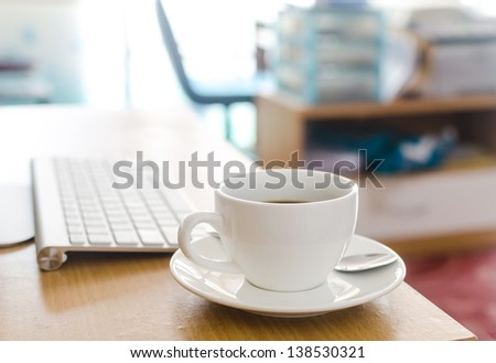 Coffee Cup on the Table with Computer Keyboard for Business Concept. - stock photo