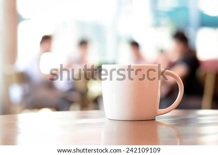 Coffee cup on the table with people in coffee shop as blur background - stock photo