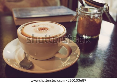 Coffee cup on the wooden table in the coffee shop - vintage style effect picture. - stock photo