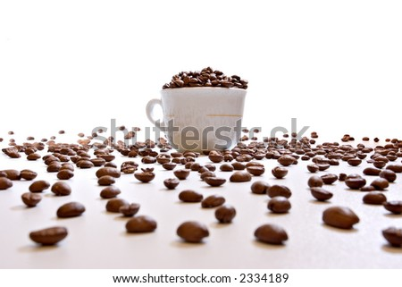 Coffee cup on with beans, on white background with deep perspective, focus on cup - stock photo