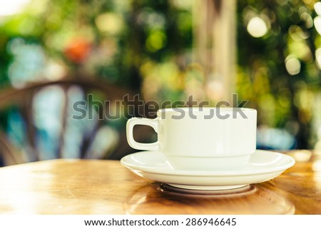 Coffee cup on wooden table outdoor background