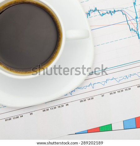Coffee cup over financial charts - close up shot - stock photo