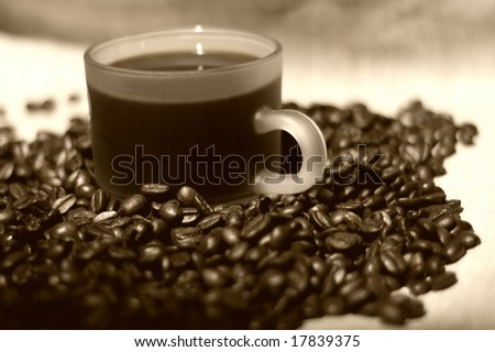 Coffee cup over roasted coffee-bean