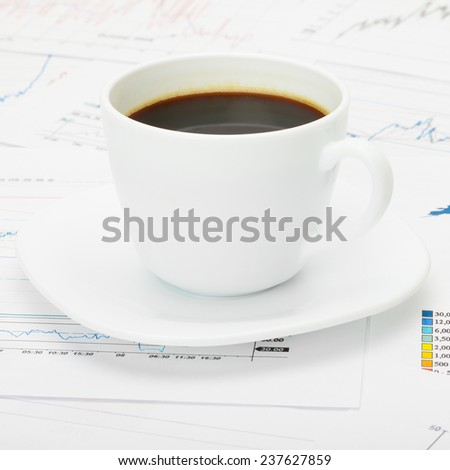 Coffee cup over world map and financial documents - business concept - stock photo