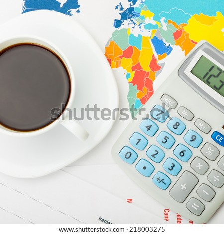 Coffee cup over world map and financial documents - view from top - 1 to 1 ratio