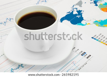 Coffee cup over world map and financial market chart - stock photo