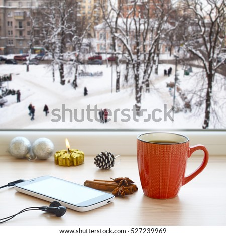 Coffee cup, smartphone and headphones on a windowsill. The view from the window on city streets