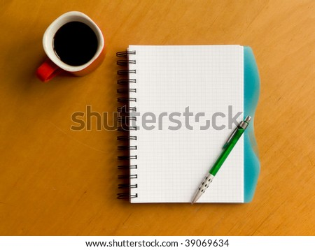 Coffee cup, spiral notebook and pen on the wooden table. Viewed from above. - stock photo