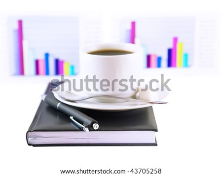 Coffee cup, standing on the personal organizer, on a back background-financial  diagrams . Isolated - stock photo