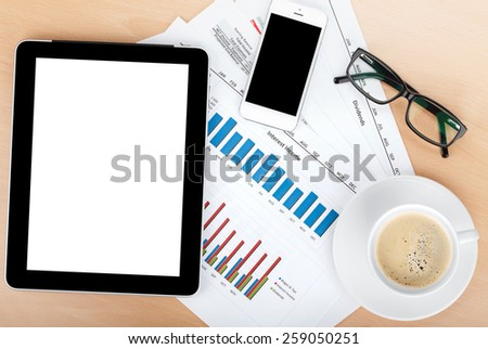 Coffee cup, tablet and glasses over papers with numbers and charts. View from above - stock photo