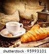 Coffee cup with a croissant and fresh coffee beans on a brown background - stock photo