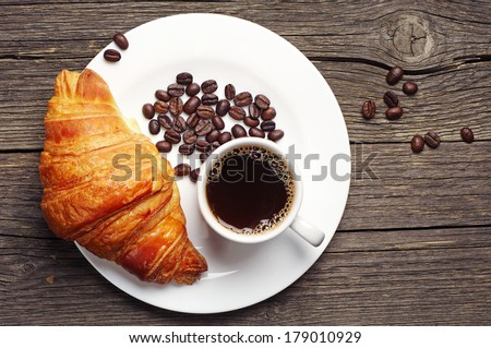 Coffee cup with a croissant on vintage wooden table. Top view - stock photo