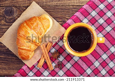 Coffee cup with a croissant on wooden table with tablecloth. Top view
