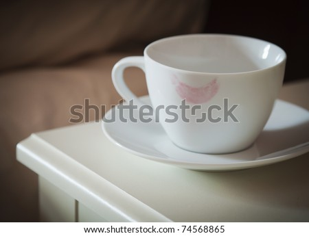 coffee cup with a lipstick mark on rim on a bedside table - stock photo