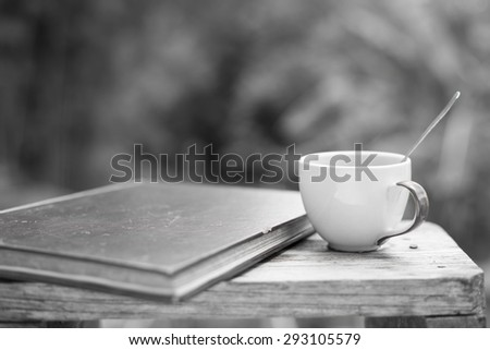 Coffee cup with a spoon and an old  book. Put on an old wooden table. in black and white tone With blur  background black and white from a tree soft. - stock photo
