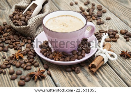 Coffee cup with anise and cinnamon on dark in wooden table - stock photo