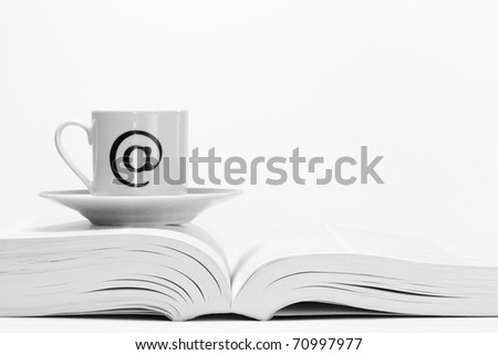 Coffee cup with 'at' symbol on open book. - stock photo